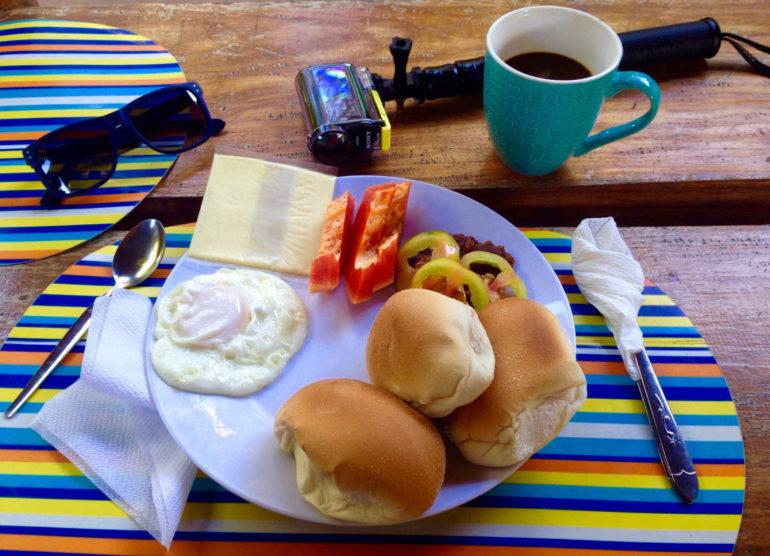 Zielony pomidor, papaya (zerwana z ogrodu 10m dalej) , trzy maślane bułeczki, plaster żółtego sera, jajko sadzone, jakieś mięsko.
